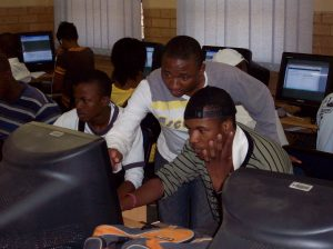 Students at the Soshanguve campus of Tshwane University of Technology help one another in the digital media lab.